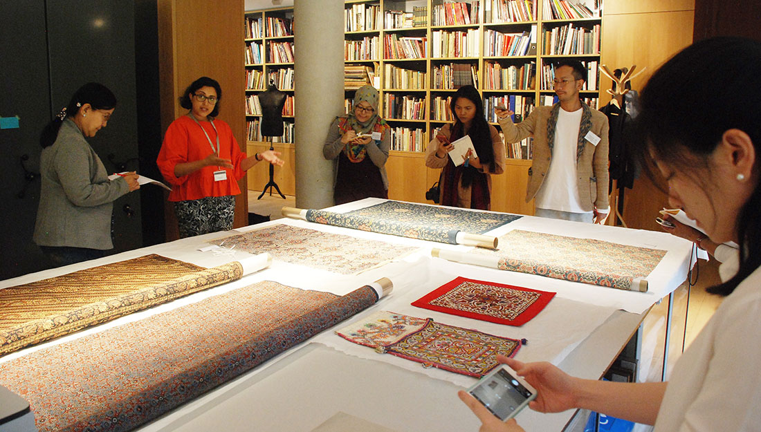 A group stand around a large table, taking notes and photos of the display of textiles.