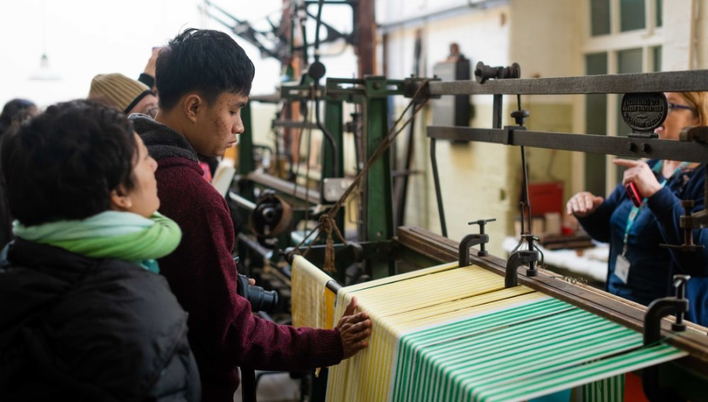 Delegates looking at an old-fashioned weaving loom