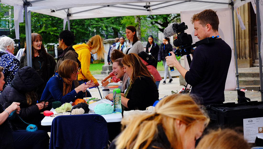 A group of people gather around a table outside making, someone is filming.