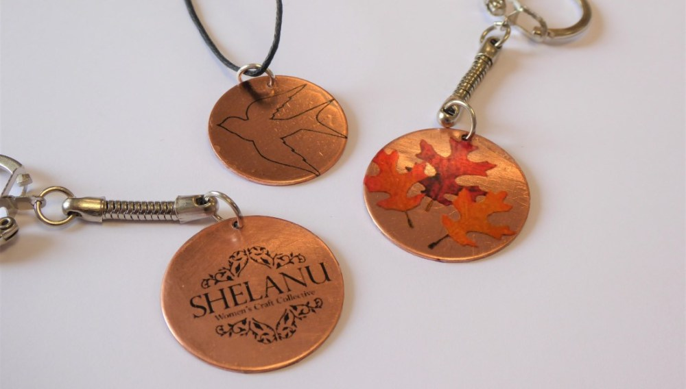 three copper discs, one with a bird, one with leaves and one that says Shelanu