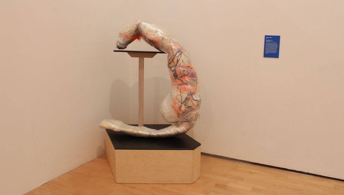 textile and cling film sculpture displayed on plinth in gallery