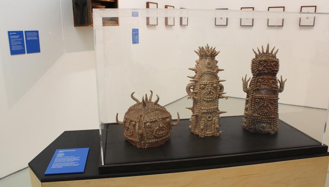 three sawada ceramic sculptures in exhibition case on plinth