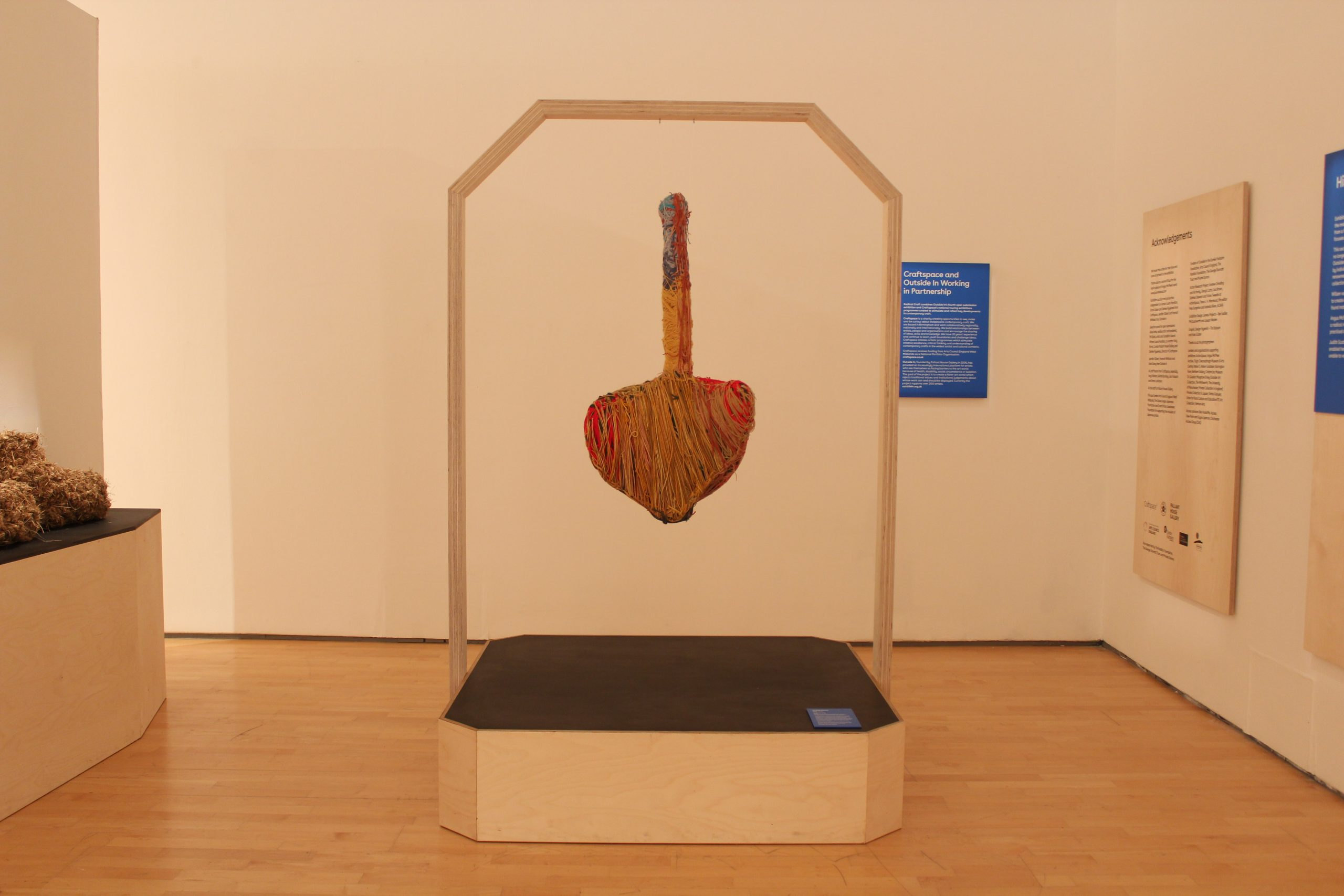 Judith Scott textile scultpure hanging from wooden plinth stand in oriel davies gallery space