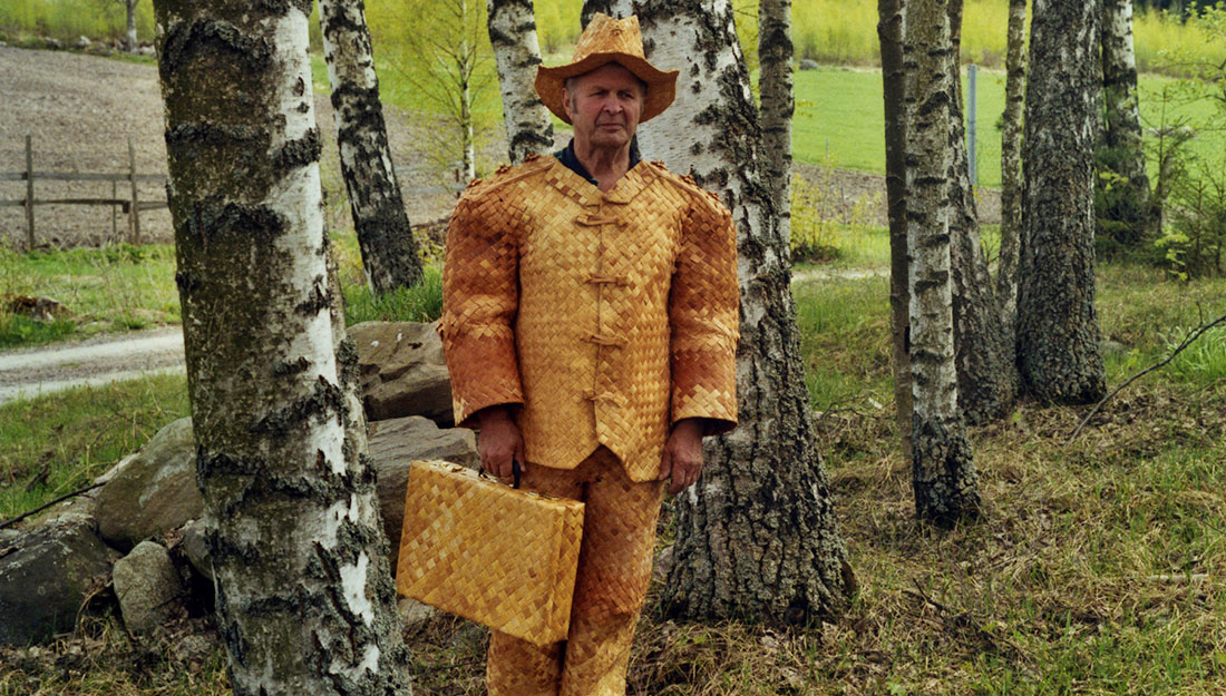 A older man, the artist, stands among birch trees dressed in a suit woven from strips of bark.