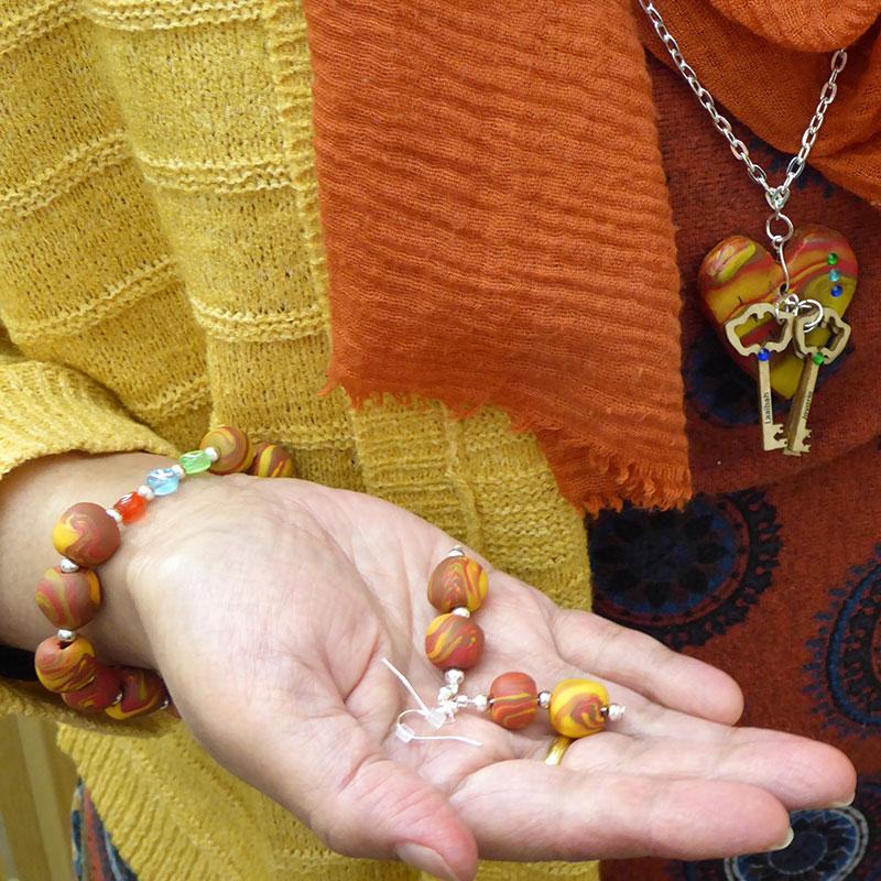 a woman wears the jewellery she has made