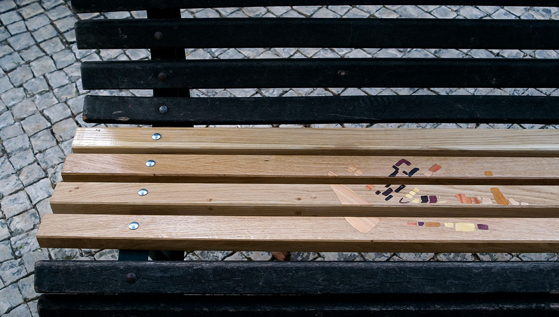 A public bench which has been repaired with new wooden slats and inlaid decoration.