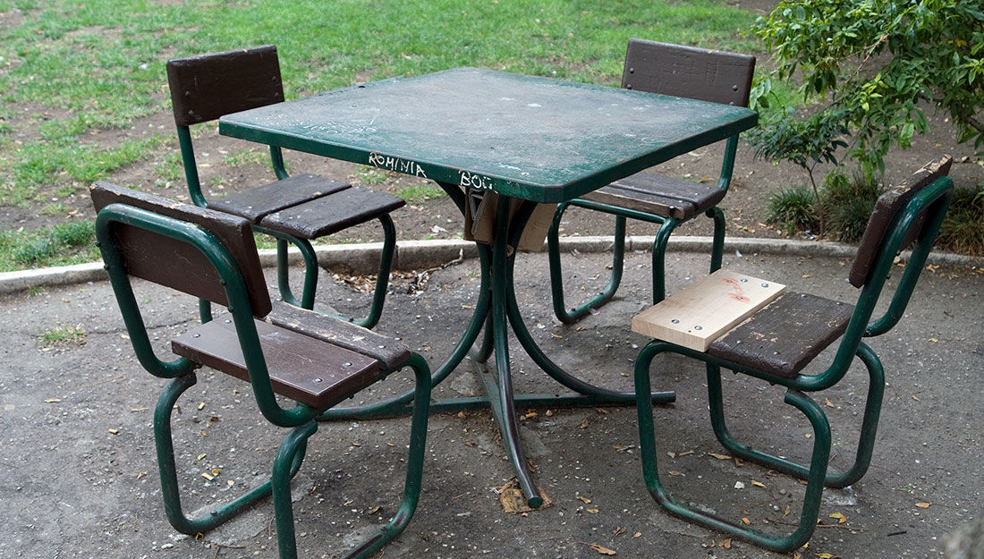 A scruffy park picnic table, the chair has been repaired.