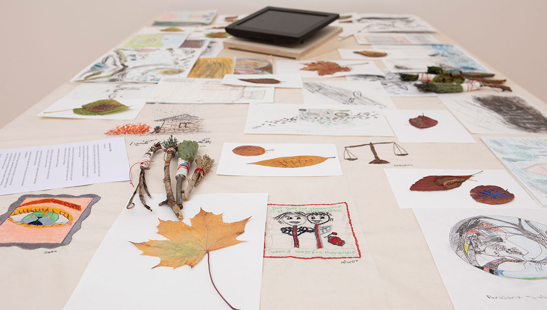 A large table is covered with leaves, paper, drawings and brushes made from twigs.