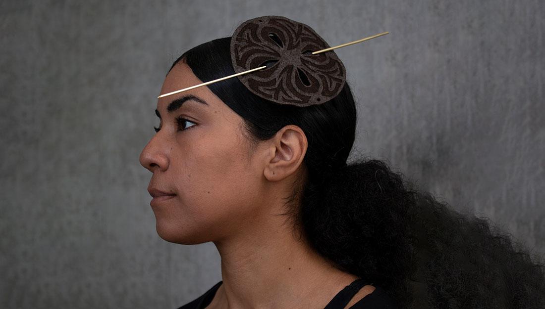 A woman wears a headpiece.