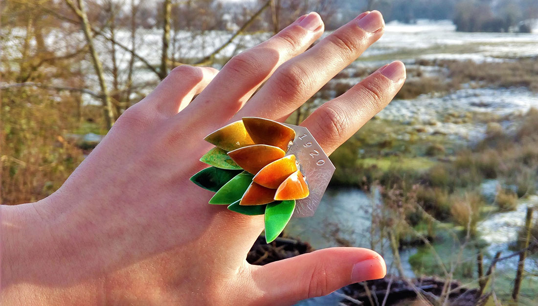 A hand with a large ring made of bright feather or leaf shapes.