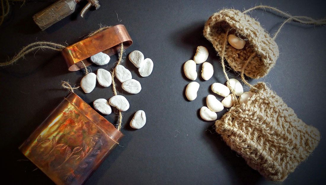 A metal case and knitted case, both containing seeds.