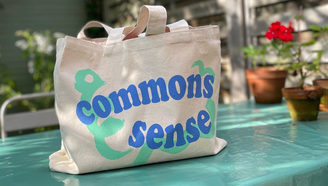 A bag sits on a table in a sunny garden, the bag has a bright design.