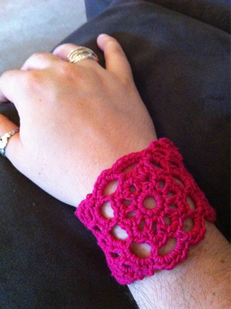 pink wrist cuff with flower-like central pattern