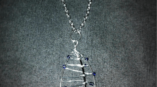 silver necklace with a 3-sided pod wrapped with wire and blue beads