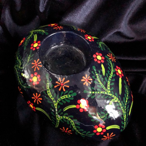 Oval tea light holder with folk art flowers pattern without candle on dark background