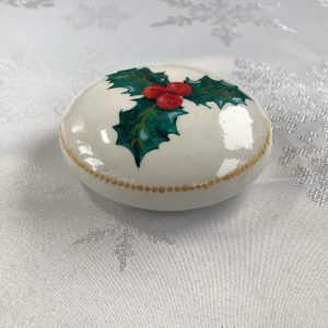Art stone painted white with holly and berries design on the surface and gold coloured dotted rim side view