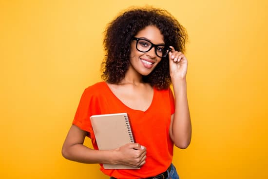 Side business ideas for teachers. Girl wearing black eyeglasses, red shirt, holding notepad.