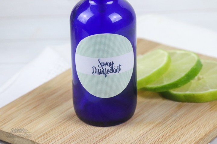 blue glass spray bottle on a wooden cutting board next to 3 round slices of lime DIY Natural Disinfectant Spray Recipe