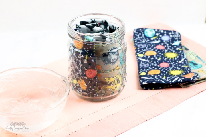 DIY Reusable Disinfecting Wipes Solution in large glass container with flannel squares