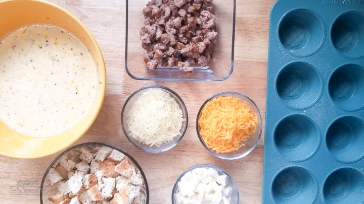 Freezer-Friendly Everything Bagel Breakfast Muffins Recipe ingredients next to a blue muffin pan on a wooden table