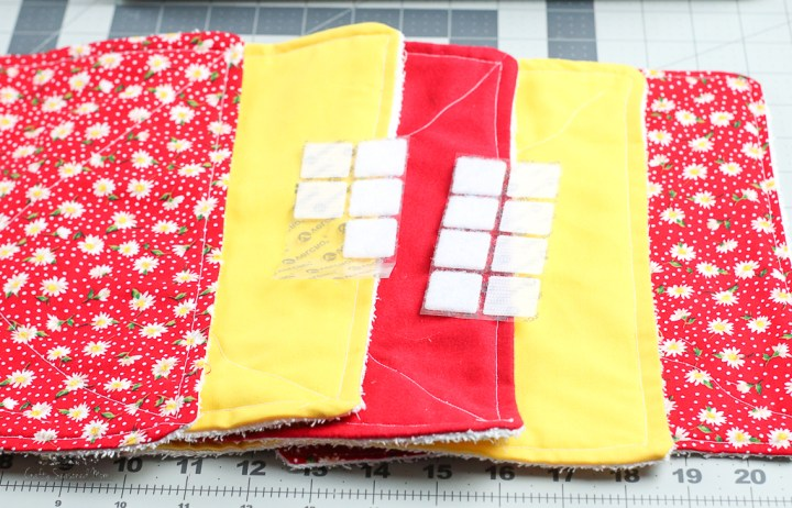red floral, solid red and solid yellow fabric with Velcro on top for How To Make Reusable Fabric Paper Towels