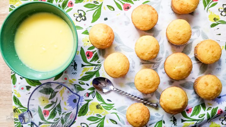 lemon pudding in a green bowl next to lemon cupcakes for the Double Lemon Jello Pudding Poke Cupcakes Recipe on a floral napkin