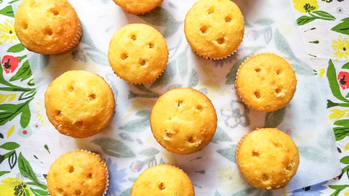 lemon cupcakes with holes in the top for the Double Lemon Jello Pudding Poke Cupcakes Recipe on a floral napkin