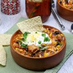 Spicy Rotisserie Chicken Chili with Black Beans Recipe in a wooden bowls topped with sour cream and green onions and a tortilla chip on a green and white gingham napkin