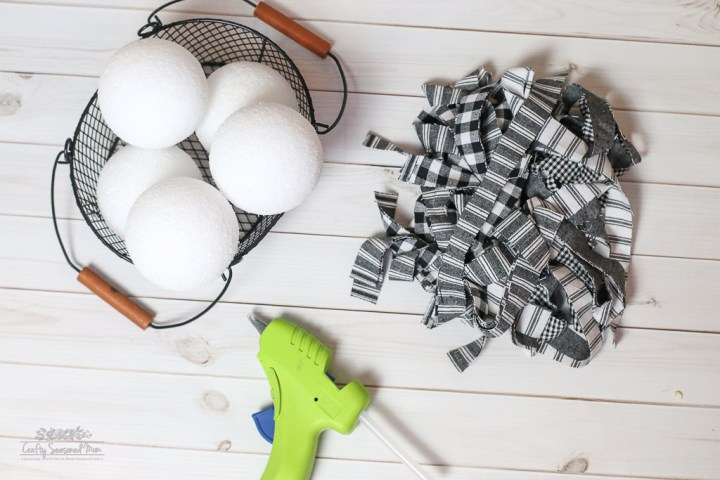 Styrofoam balls in a wire basket, strips of black and white fabric and a green hot glue gun on a white wooden surface for the Simple DIY Rustic Farmhouse Style Primitive Rag Balls