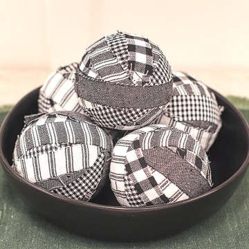 A black bowl holding 5 completed Simple DIY Rustic Farmhouse Style Primitive Rag Balls on a green placemat