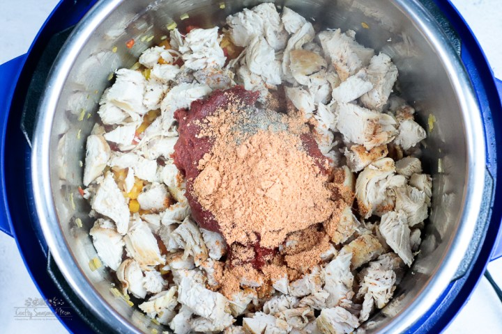chicken, tomato sauce and spices in the instant pot for the Spicy Rotisserie Chicken Chili with Black Beans Recipe