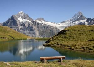 Berge, ein See und davor steht eine Holzbank