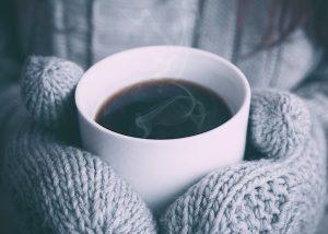 Hände in Handschuhen umfassen eine warme Tasse Kaffee