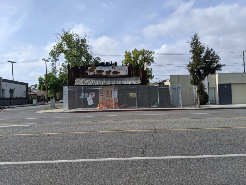 Tinhorn Flats, ringed with chainlink, doors barricaded with plywood and sandbags.