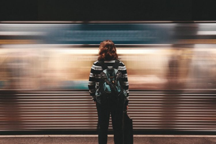 Person waiting for direction in front of a train