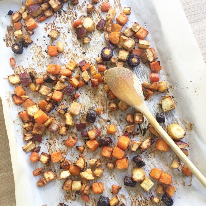 maple and cumin roasted vegetables with a wooden spoon
