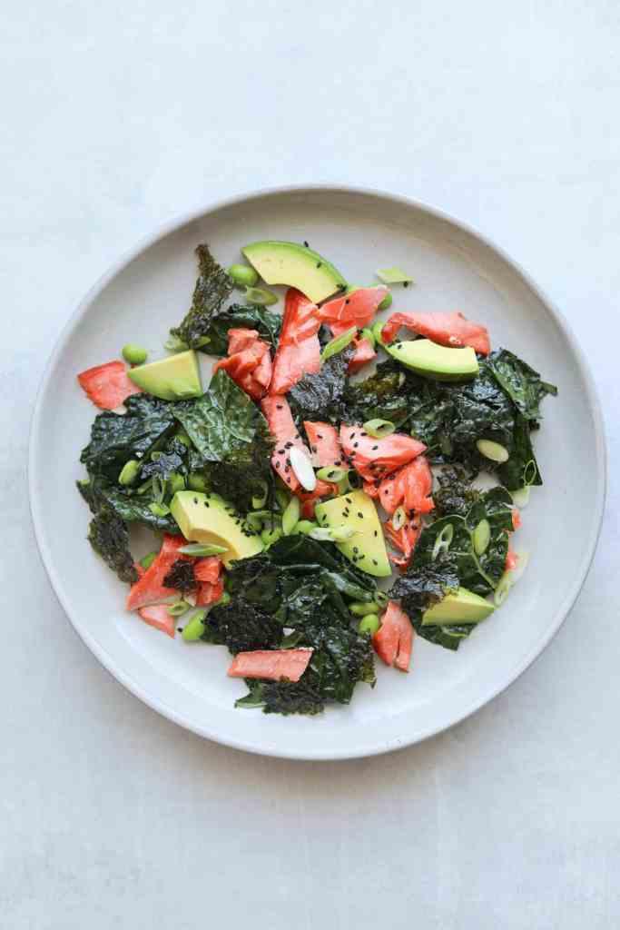 kale salad on a plate with salmon, avocado and sesame seeds