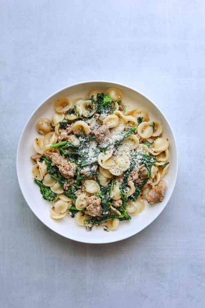 A bowl of pasta with broccoli rabe, sausage orecchiette and parmesan