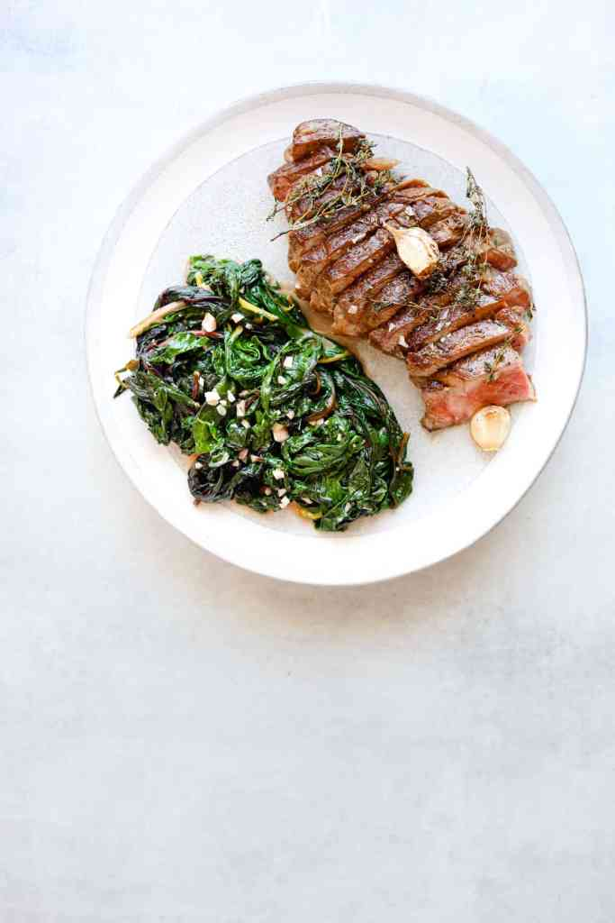ribeye on a plate with garlicky greens