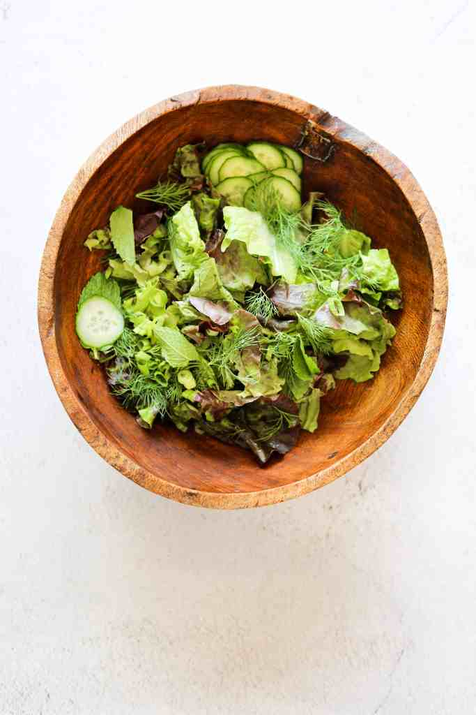 Lettuce, herbs and cucumbers in a wooden salad bowl.