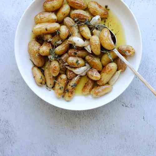 Roasted Fingerling Potatoes with Garlic and Rosemary in a white bowl with a gold spoon