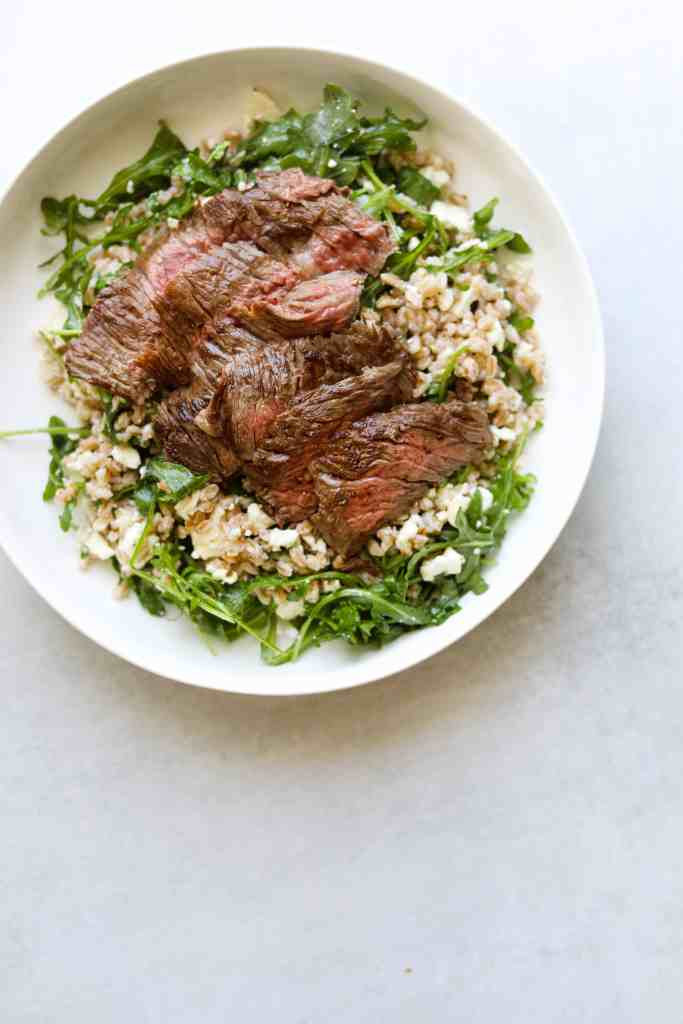 Five-Ingredient Steak Salad with Farro, Arugula, and Feta In a white bowl