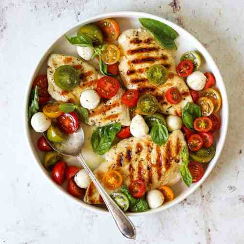 A white platter with three grilled chicken breasts topped with marinated tomatoes, fresh mozzarella cheese and basil.