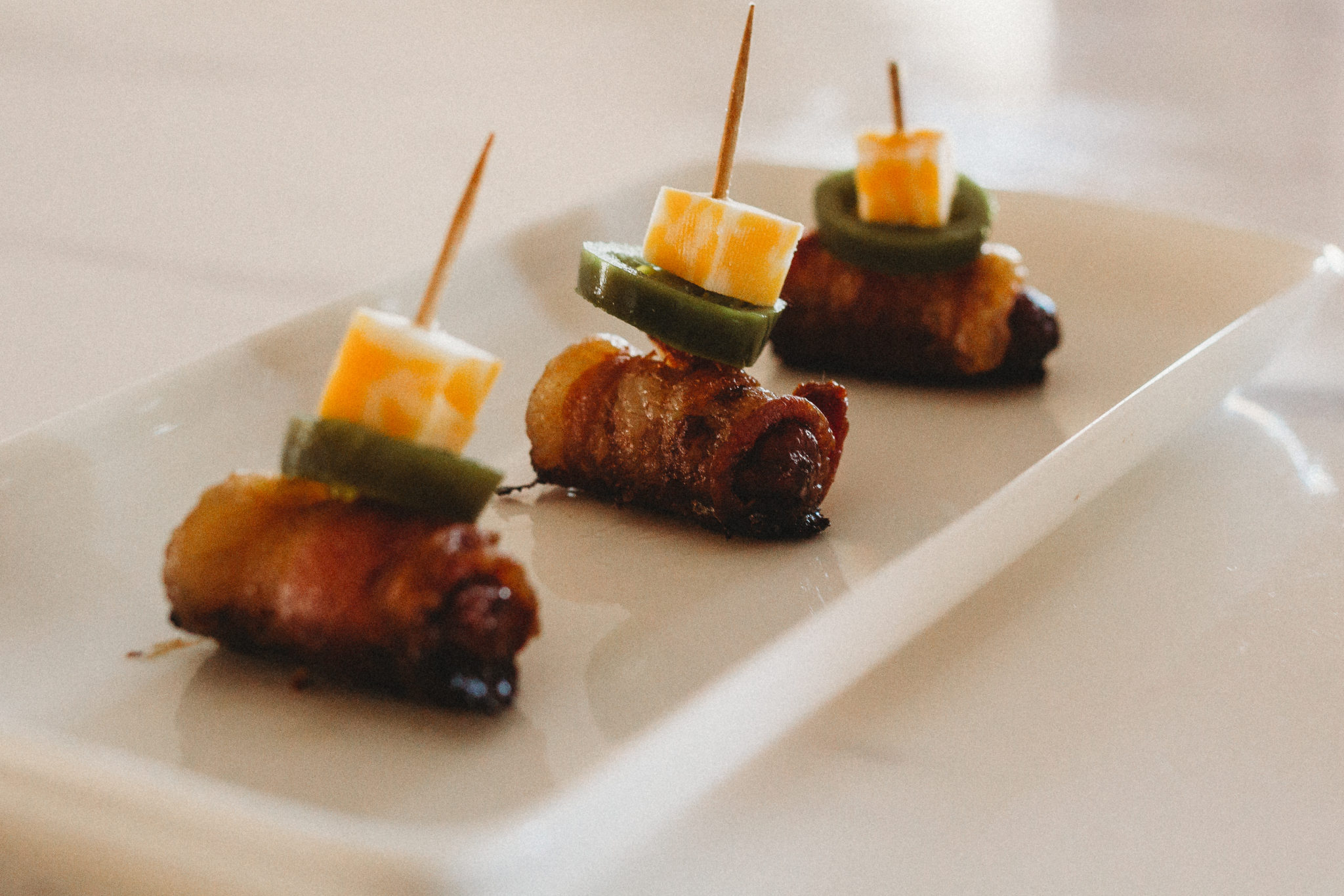 Celebrate the Big Game with quick and easy appetizers like this fun take on the jalapeno popper using Litl Smokies sausages wrapped in bacon and topped with cheddar cheese and jalapeno. #ad #TysonWinningLineup #Walmart