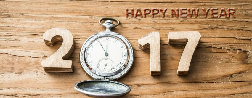 Happy New Year 2017 with a clock and wooden background