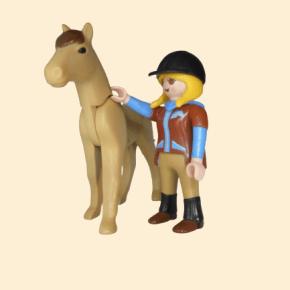 Jeune fille blonde en tenue d'équitation avec son cheval
