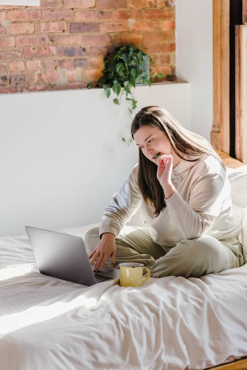 woman surfing internet on laptop while eating
