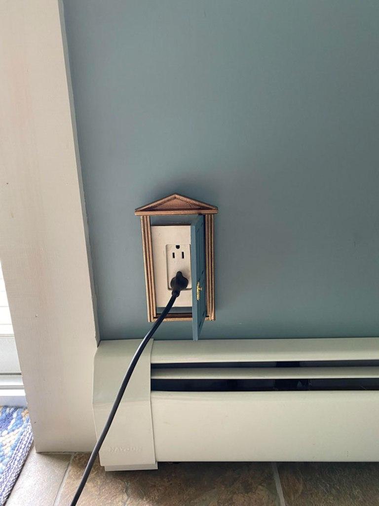 Des prises électriques camouflées par des petites portes de maison de poupée.