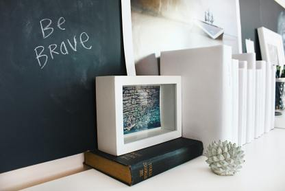 blackboard with be brave written in white chalk. Box with cut out with a picture of words inside. Box sitting on a black book that is sitting on a white desk. Books set up vertically stacked next to box.