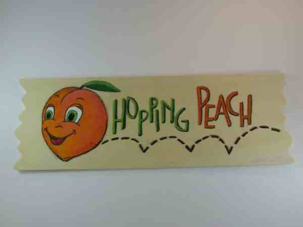 """Image: painted sign with hopping peach and text """"Hopping Peach."""""""